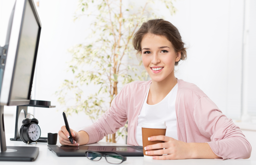 Female member of Generation Z sat at her computer with a coffee.