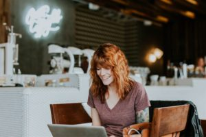 A woman writing her blog in a coffee shop. Tips for improving your blog writing.